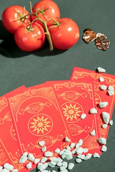 High angle tarot cards next to tomatoes