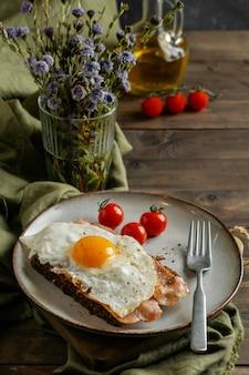 Вкусный завтрак под высоким углом с яйцом и беконом