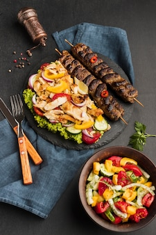 High angle of tasty kebab on slate with other dish and cutlery