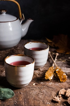 High angle tea in cups with crystallized sugar