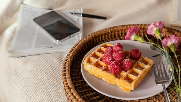 High angle tea and waffle with raspberry