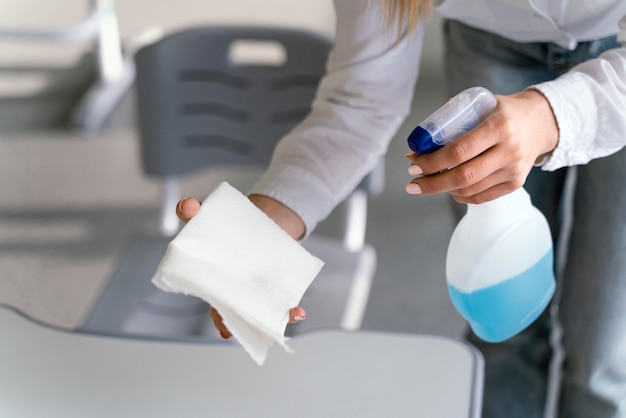 High angle of teacher disinfecting school benches in classroom