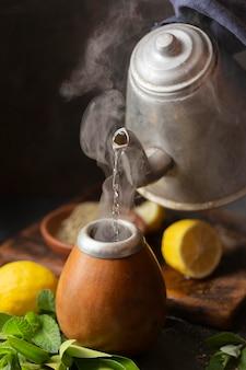 Чайник под высоким углом наливает горячую воду в заварочный узел
