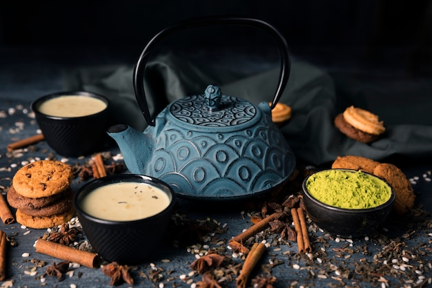 High angle teapot surrounded by bowls and tea cups