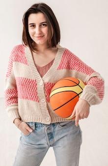 Высокий угол девушка держит баскетбольный мяч