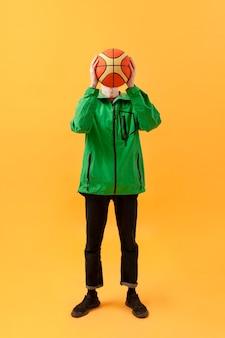 Высокий угол подросток играет с баскетбольным мячом