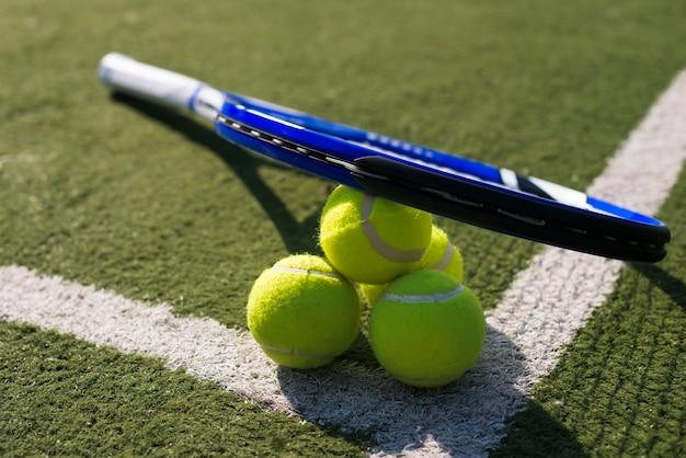 High angle tennis racket and balls on the ground