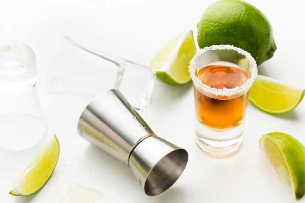 High angle tequila shot with lime slices and salt
