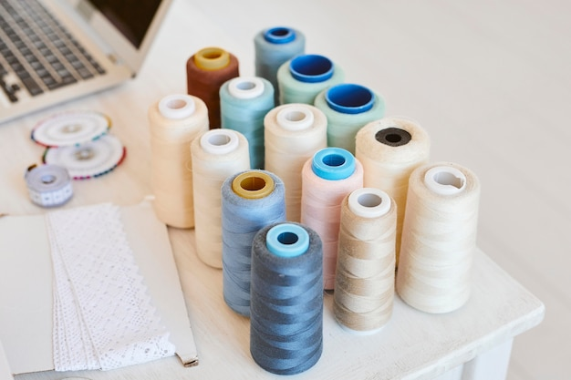 High angle of thread spools on table with laptop in atelier