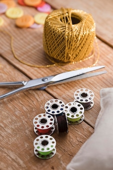 High angle of thread with scissors and sewing machine shuttles