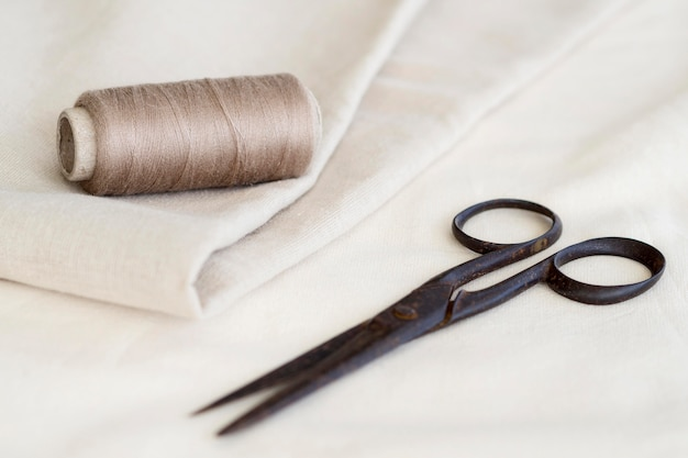 High angle of thread with textile and scissors