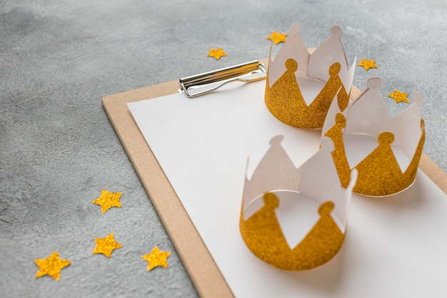 High angle of three crowns for epiphany day with notepad