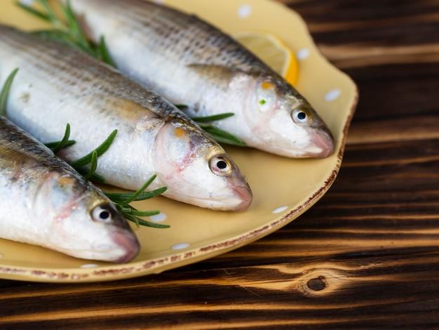 Высокий угол три рыбы на тарелку с травами