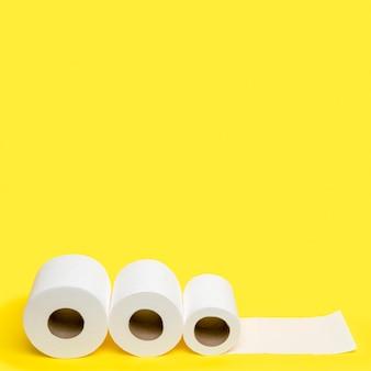 Un angolo alto di tre rotoli di carta igienica con spazio di copia