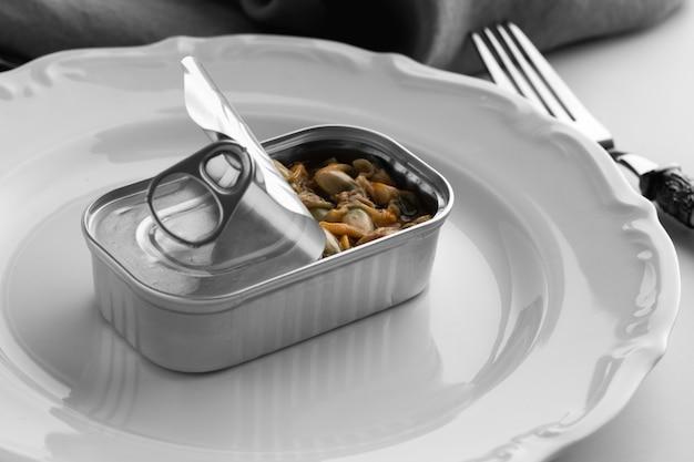 Barattolo di latta ad alto angolo con cibo sul piatto con forchetta