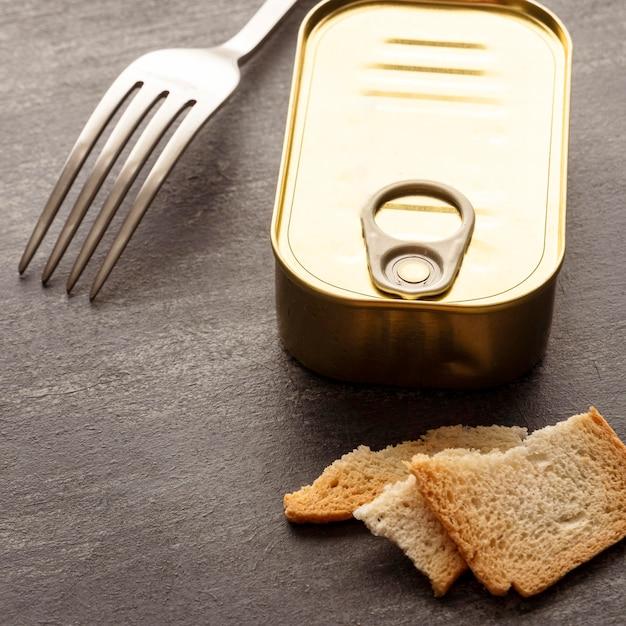 Barattolo di latta ad alto angolo con pane tostato e forchetta