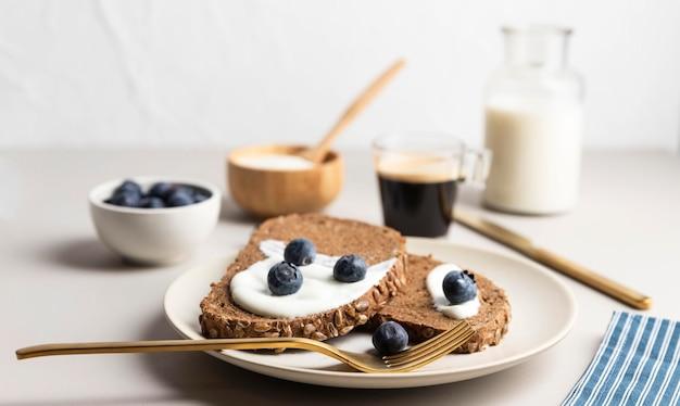 Alto angolo di pane tostato sulla piastra con mirtilli e latte