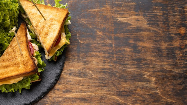 High angle of tomatoes and salad triangle sandwiches on slate with copy space