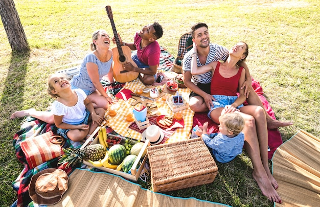 High angle top view of happy families having fun with kids at pic nic barbecue party