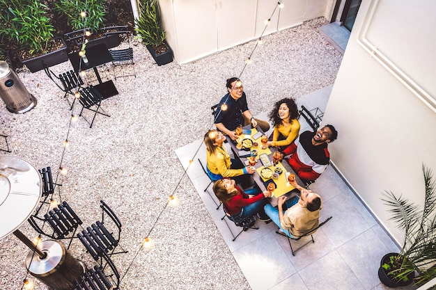 Высокий угол обзора счастливых друзей, пьющих коктейли и веселящихся на вечеринке в саду ресторана