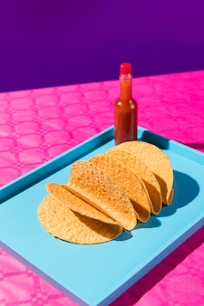High angle tortillas and sauce bottle on tray
