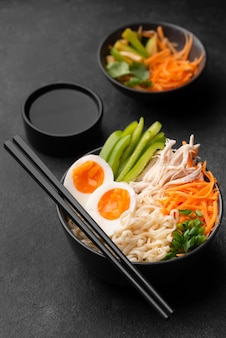 High angle of traditional asian dish with chopsticks and eggs