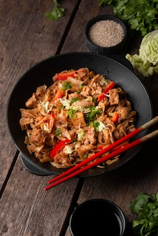 Alto angolo del piatto asiatico tradizionale con le bacchette