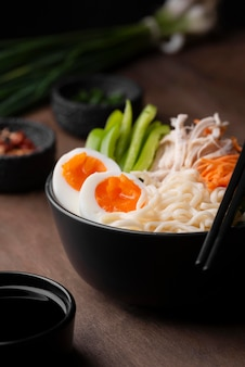 High angle of traditional asian dish with eggs in noodles