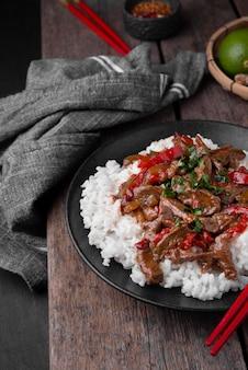 Alto angolo di riso asiatico tradizionale con carne e tessuto