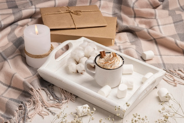 High angle of tray with coffee with whipped cream and candle