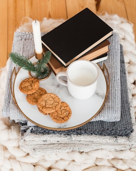 High angle tray with cookied and milk and stack of books
