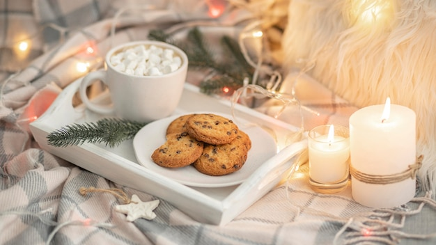 High angle of tray with cookies and mug with marshmallows