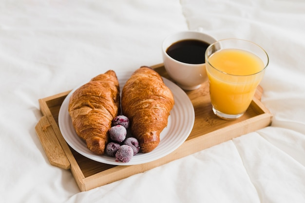 High angle tray with croissants orange juice and coffee