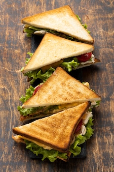 High angle of triangle sandwiches with tomatoes