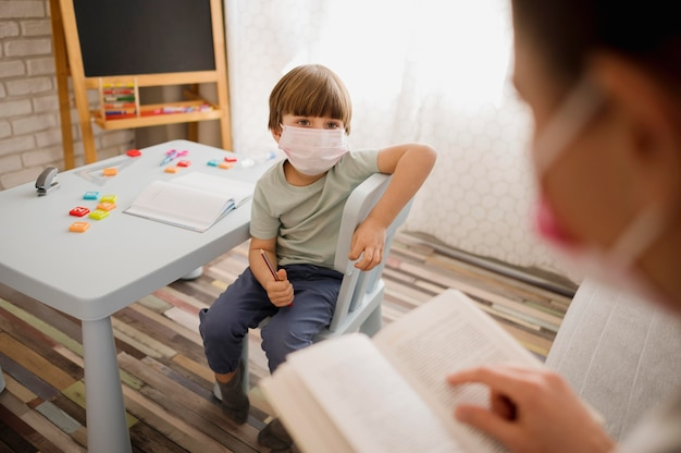 High angle of tutor with medical mask teaching child at home
