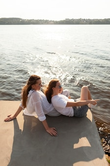 High angle of two female friends spending time together by the lake