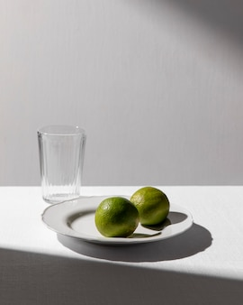 High angle of two limes on plate with clear glass