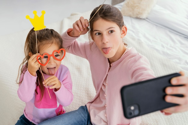 High angle of two sisters at home taking selfie
