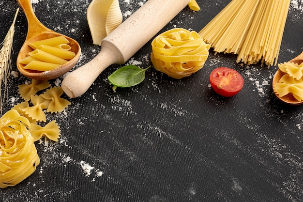 High angle uncooked pasta with rolling pin and copy space