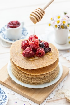 High angle vertical closeup shot of raw vegan pancakes with honey and berries
