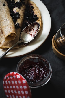 High angle vertical shot of delicious crepes with blueberry jam on a black surface