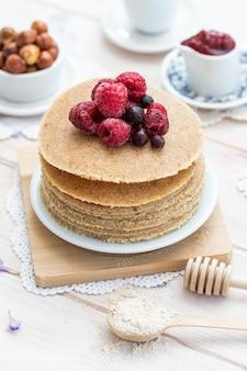 꿀과 딸기와 함께 원시 채식주의 팬케이크의 높은 각도 수직 샷