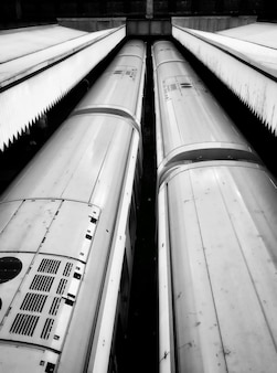 High angle vertical shot of  two trains in a train station in black and white