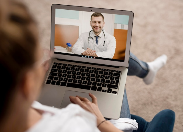 High angle video call on laptop with doctor