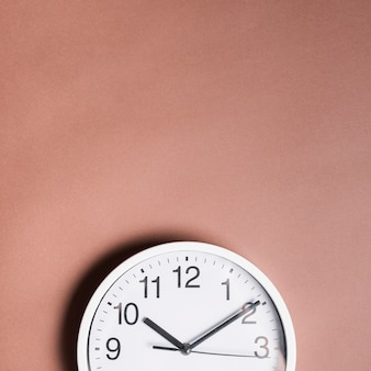 High angle view of an alarm clock on brown backdrop