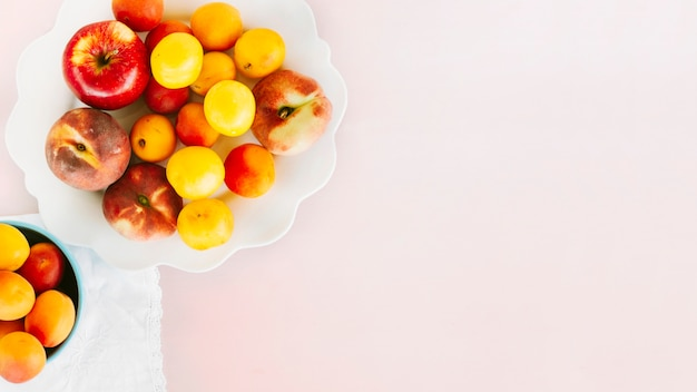 High angle view of apple; peach and plum on pink background