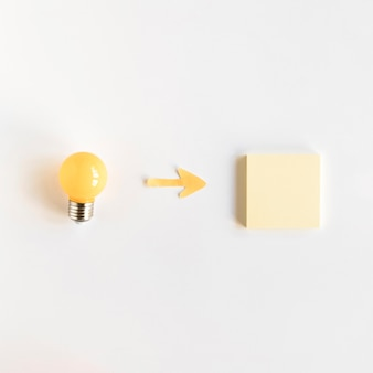 High angle view of arrow symbol between light bulb and adhesive note