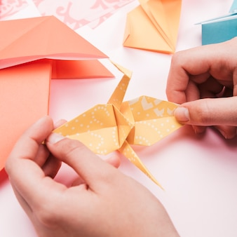 High angle view of artist hand holding origami paper bird