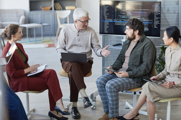 戦略会議中に輪になって座っている現代の多様なビジネスチームのハイアングルビュー、中央のシニアビジネスマンに焦点を当てる