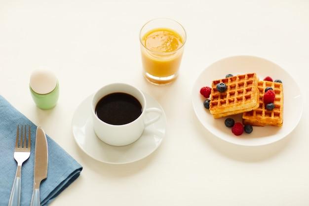 白いテーブルの上のブラックコーヒーのカップの横に甘いデザートワッフル、卵、オレンジジュースとおいしいグルメ朝食のハイアングルビュー